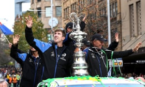 Members of Emirates Team New Zealand parade the America's Cup yachting trophy through the streets of Auckland.