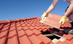 A worker replaces red roof tiles on a house