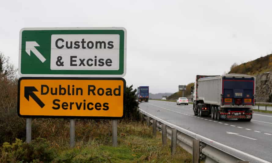 """A lorry passes a sign on a main road outsid outside Newry, Northern Ireland, on November 14, 2018 pointing towards an old customs and excise station near the border between Northern Ireland and Ireland. - British Prime Minister Theresa May defended her anguished divorce deal with the European Union before rowdy lawmakers on Wednesday before trying to win the backing of her splintered cabinet with the so-called """"Irish backstop"""" arrangement to guard against the imposition of a hard border between Ireland and Northern Ireland one of the contentious issues, according to reports."""