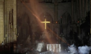 Smoke rises around the altar in front of the cross inside Notre Dame