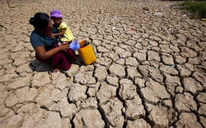 Yangon, Burma - A woman and child rest on their way to fetch water at a creek in Twantay township
