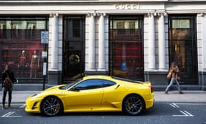 A yellow Ferrari parked outside Gucci on Old Bond Street in London