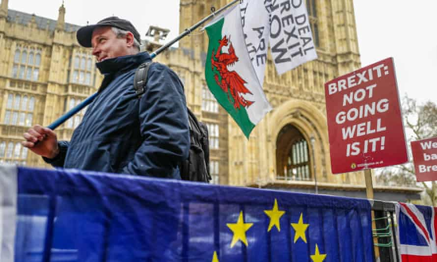 A pro-leave demonstrator walks past pro-remain placards opposite the Houses of Parliament on 3 April 2019.