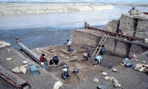 Spring 1985, British School excavations on the Tigris in advance of the Eski Mosul Dam. Excavators work in a large square trench next to a wide fast-flowing river.