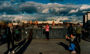 Tourists pose and take pictures on a bridge across the Moskva river,