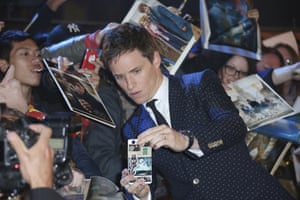 Actor Eddie Redmayne poses for selfies with fans on the red carpet.