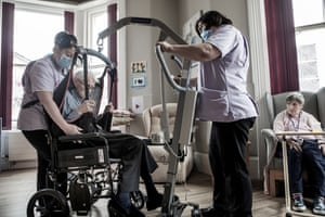 Care workers help 93-year-old Reg Stones from his armchair into a wheelchair before taking him back to his room.