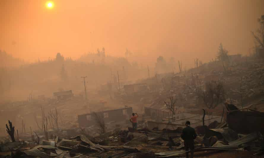 People walk amid the remains of burnt down buildings after a forest fire in Santa Olga on 26 January. The impoverished village is surrounded by hugely profitable plantations.