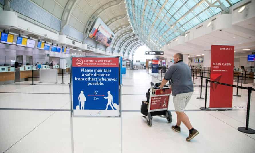 A man pushes a baggage cart wearing a mandatory face mask at Toronto Pearson international airport.