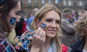 Young woman having face painted with a saltire
