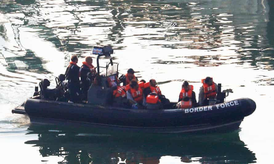 A group of men are brought to shore by Border Force officers at the Port of Dover.