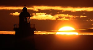 Northumberland, UK: The sun rises behind the lighthouse on Blyth Pier on the last day of the meteorological summer in the northern hemisphere