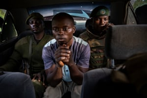A Congolese man arrested for alleged links with the Allied Democratic Forces (ADF), an Islamist terror group, sits in a car on his way to be interrogated by the army.