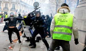 """A protester with a slogan saying """"Tired of taxes, Macron resign!!!"""" is confronted by baton wielding police."""