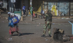 An armed soldier patrols a street in Harare during protests.