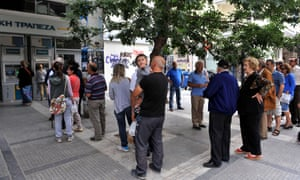 People stand in a queue to use ATM machines at a bank in Thessaloniki on June 27, 2015.