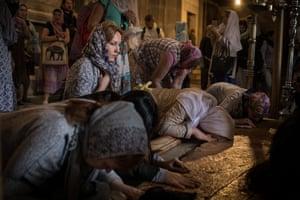 Women in headscarves kneeling and bending their heads