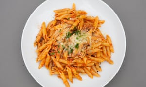 A large round white plate of penne with sausage sauce.