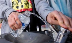 Students refilling a water bottle at a fountain.