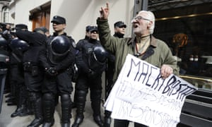 A man protests against a police search at the home of Senator and former president Cristina Fernandez. The search was part of a larger corruption investigation.