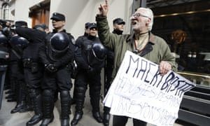 A protester holds a sign criticising Mauricio Macri in Buenos Aires