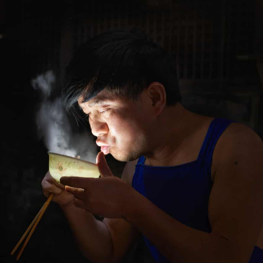 One of the teashop workers enjoys a lunchtime bowl of soup, China