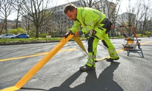 A worker lays a temporary cycle lane on a main road in Berlin