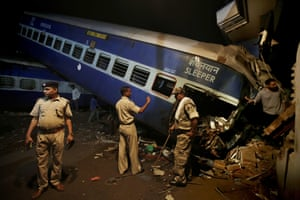 Police officers stand guard near the upturned coaches of the Kalinga-Utkal Express, after a passenger train derailed near Khatauli