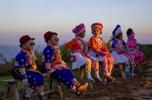 Chiang Rai, Thailand Hill tribe children dressed in traditional attire wait at a mountain viewpoint to pose with tourists as the sun rises at Phu Chi Fa viewpoint