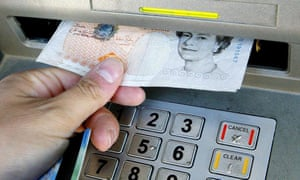 a person with withdraws cash from an ATM