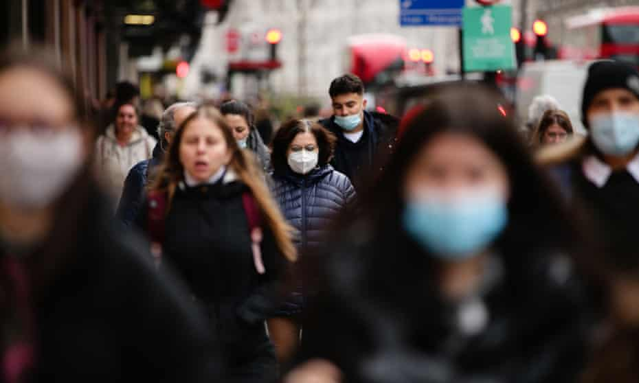 People in a busy shopping street, some wearing masks.