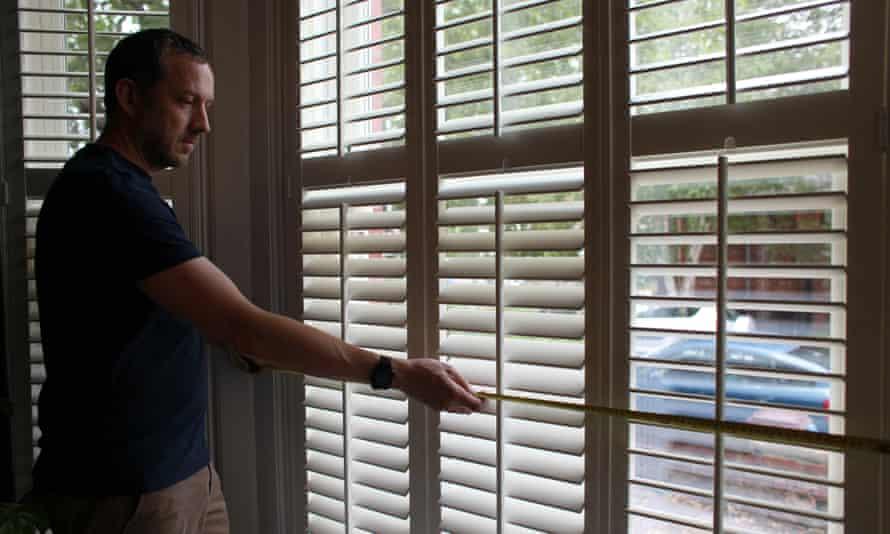Richard Shears, measuring a window as he assesses a house for retrofitting