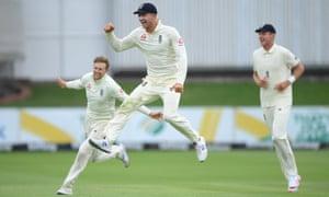 England captain Joe Root (l) celebrates with Joe Denly (c) after taking the wicket of Quinton de Kock
