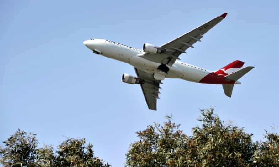 qantas plane flies against blue sky