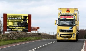 A lorry passes a billboard by the campaign group Border Communities Against Brexit