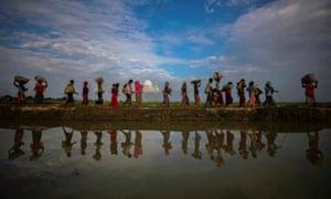 Rohingya refugees walk alongside paddy fields after fleeing from Myanmar into Palang Khali, Bangladesh, November 2017
