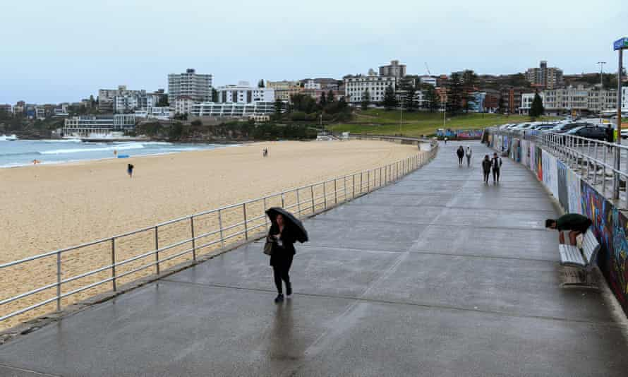 People walk along an empty Bondi beach foreshore