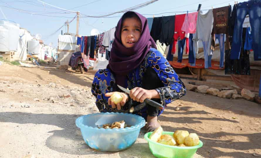 A Syrian refugee peels potatoes at a refugee camp in Zahle in the Bekaa valley, Lebanon