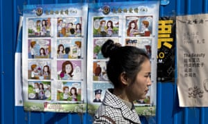 A woman walks past a poster in Beijing warning against foreign spies.