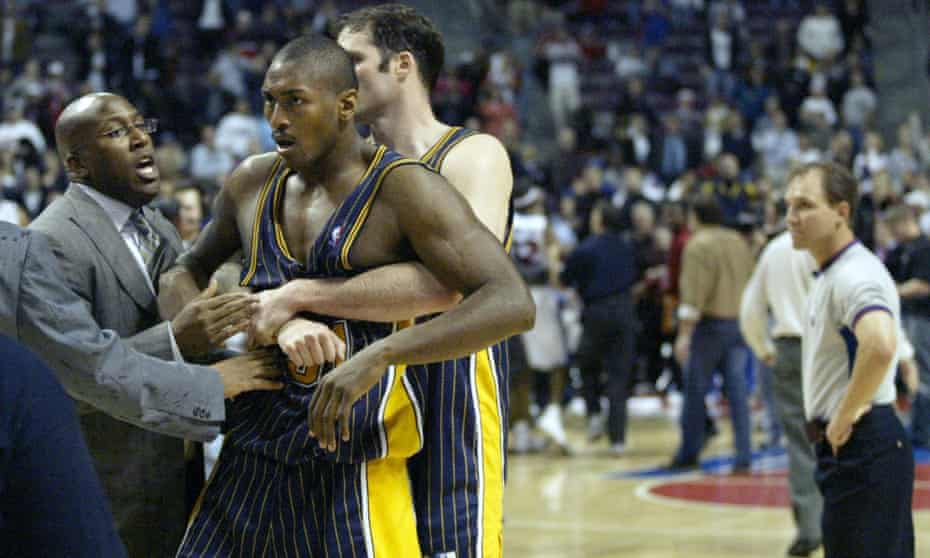 So astonishing it could never be scripted ... Indiana Pacers' Ron Artest is restrained by Austin Croshere after the team's game with Detroit Pistons in 2004.