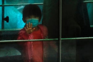 Hong Kong, China A child waves from a vehicle carrying residents, evacuated to combat coronavirus, from a Cheung Hong housing estate