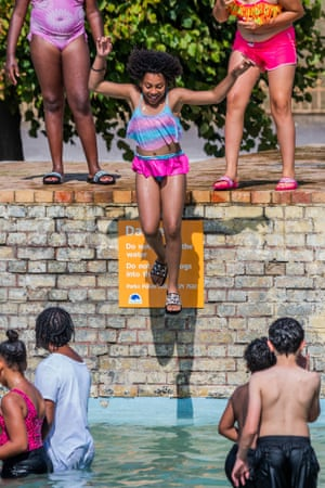Families jump into Battersea Park's ornamental ponds as a way of cooling down