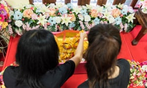 Phatcharakorn Likanrapichitkun (left) and her mother, Varunthip Manthin, place marigold flowers in a small casket containing their dog Fou Fou at Pet Funeral Thailand. The family dog was killed suddenly by a motorcycle in the early morning hours.