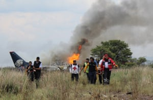 Rescue workers stretcher an injured person away from the site where an Aeromexico airliner crashed in Durango, Mexico