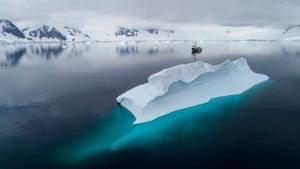 Greenpeace ship the Arctic Sunrise sails past an iceberg in Charlotte Bay, Antarctic Peninsula
