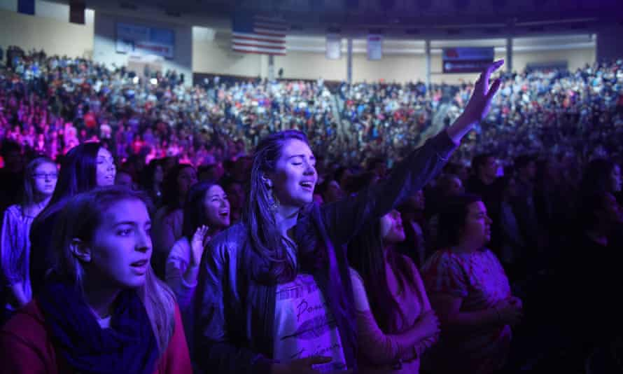 People listen to a Christian song during a convocation on the campus of Liberty University, founded by Jerry Falwell.