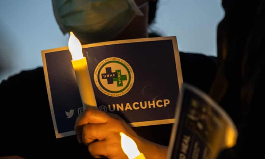 A nurse from the Kaiser Permanente Woodland Hills medical center holds an electric candle during a candlelight vigil in memory of those lost during the coronavirus pandemic in Woodlands Hills, California, in May.