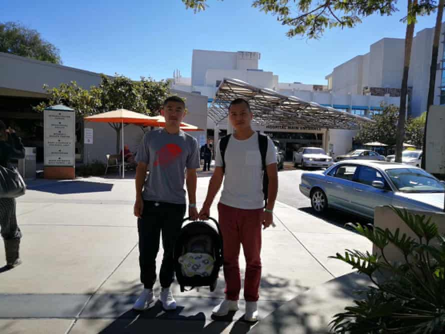 Li, left, and Xu outside the hospital with their newborn.
