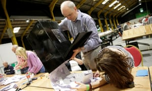 Electoral workers empty a ballot box at the count centre as votes are tallied following the referendum on liberalising abortion law in Ireland.
