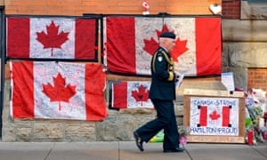 Canadian flags and flowers line the sidewalk outside the home base of the Argyll and Sutherland Highlanders at the John W. Foote Armoury in Hamilton, Canada